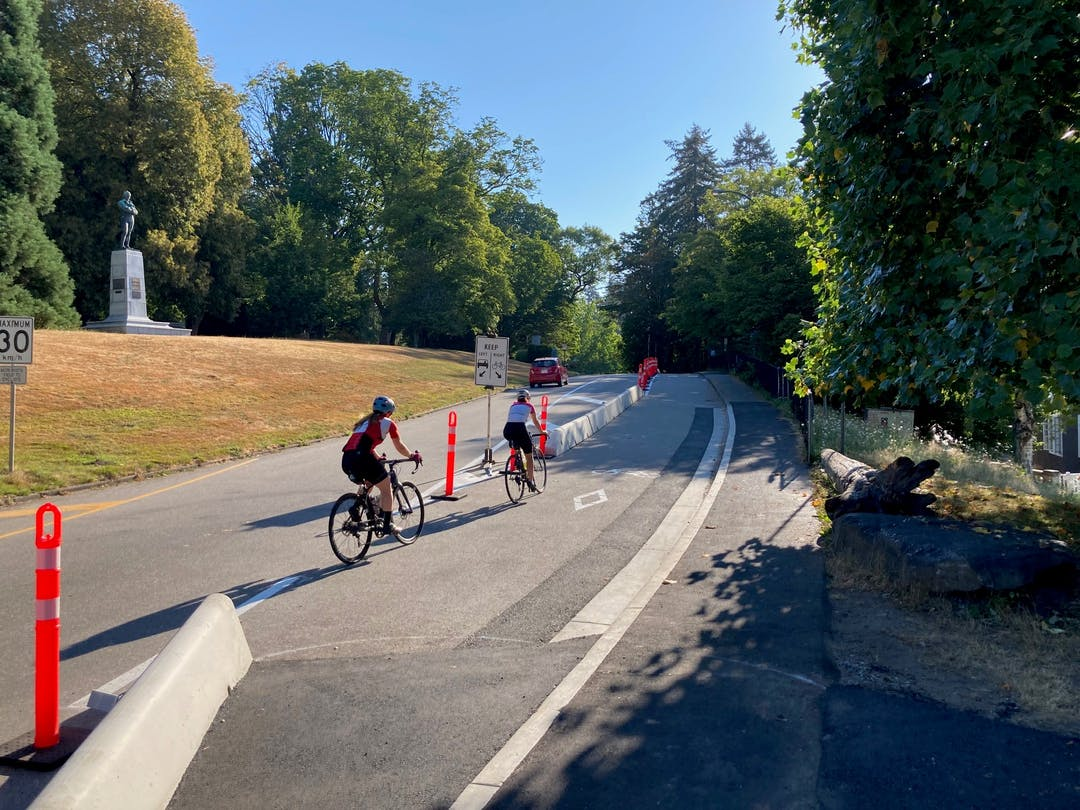 Cyclists travel on the bike lane on Stanley Park Drive with concrete barriers to separate them from the vehicle traffic lane