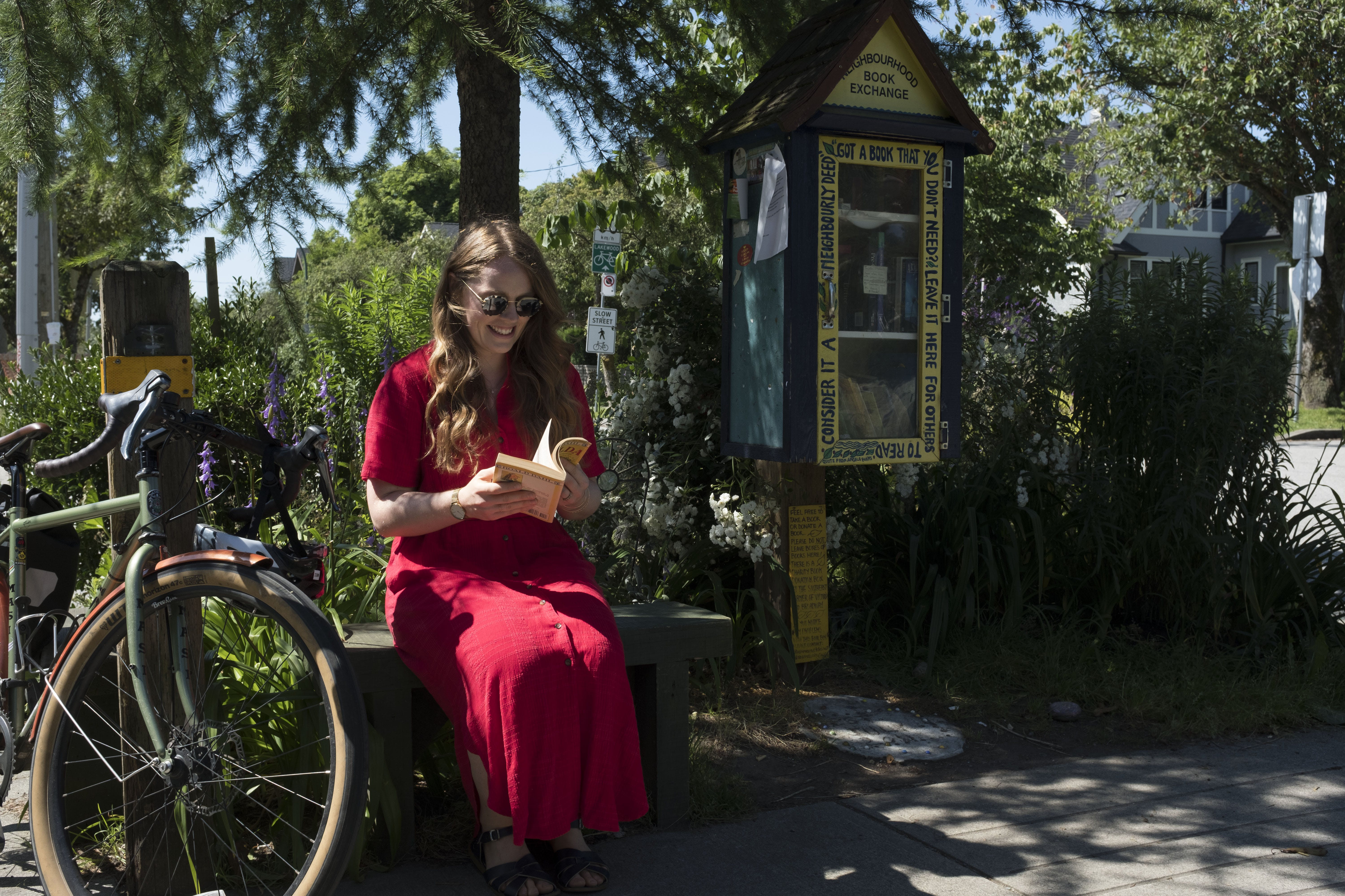 A resident reading a book near Book Exchange pop-up at Lakewood Drive and Charles Street.