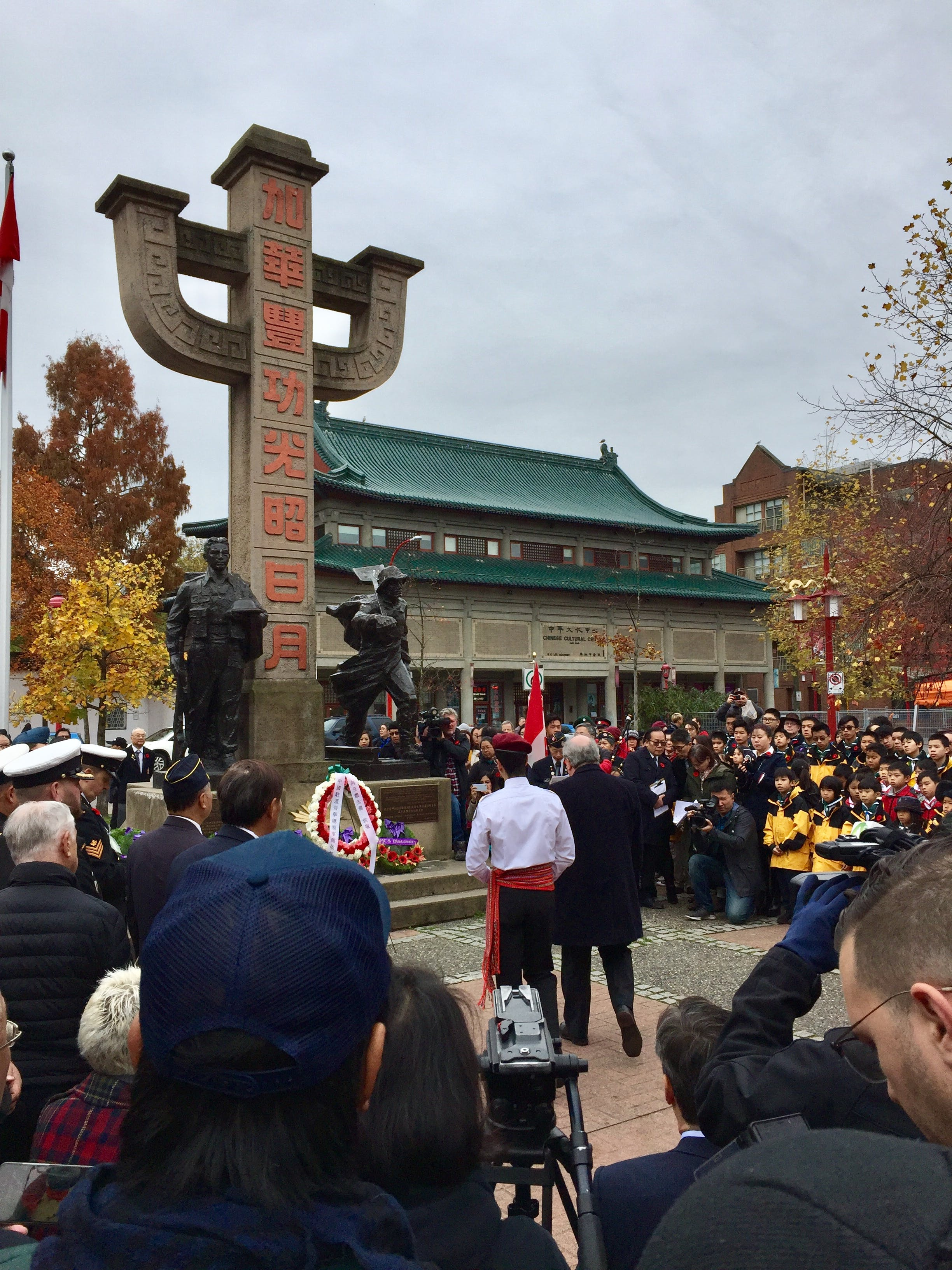 Several people surround the monument in Memorial Plaza, honouring the contributions of Chinese-Canadians to Canada