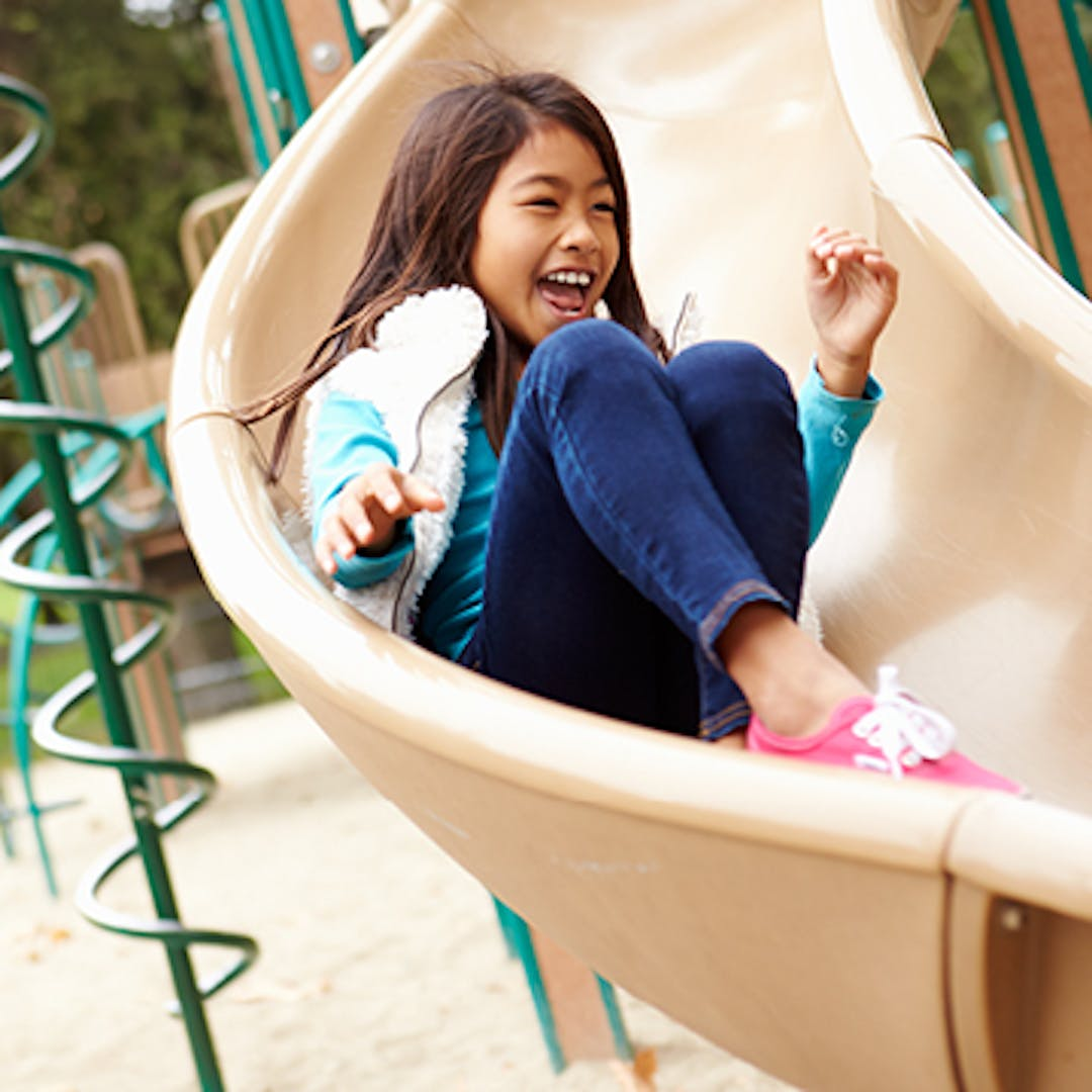 A young laughing girl slides down a playground slide.