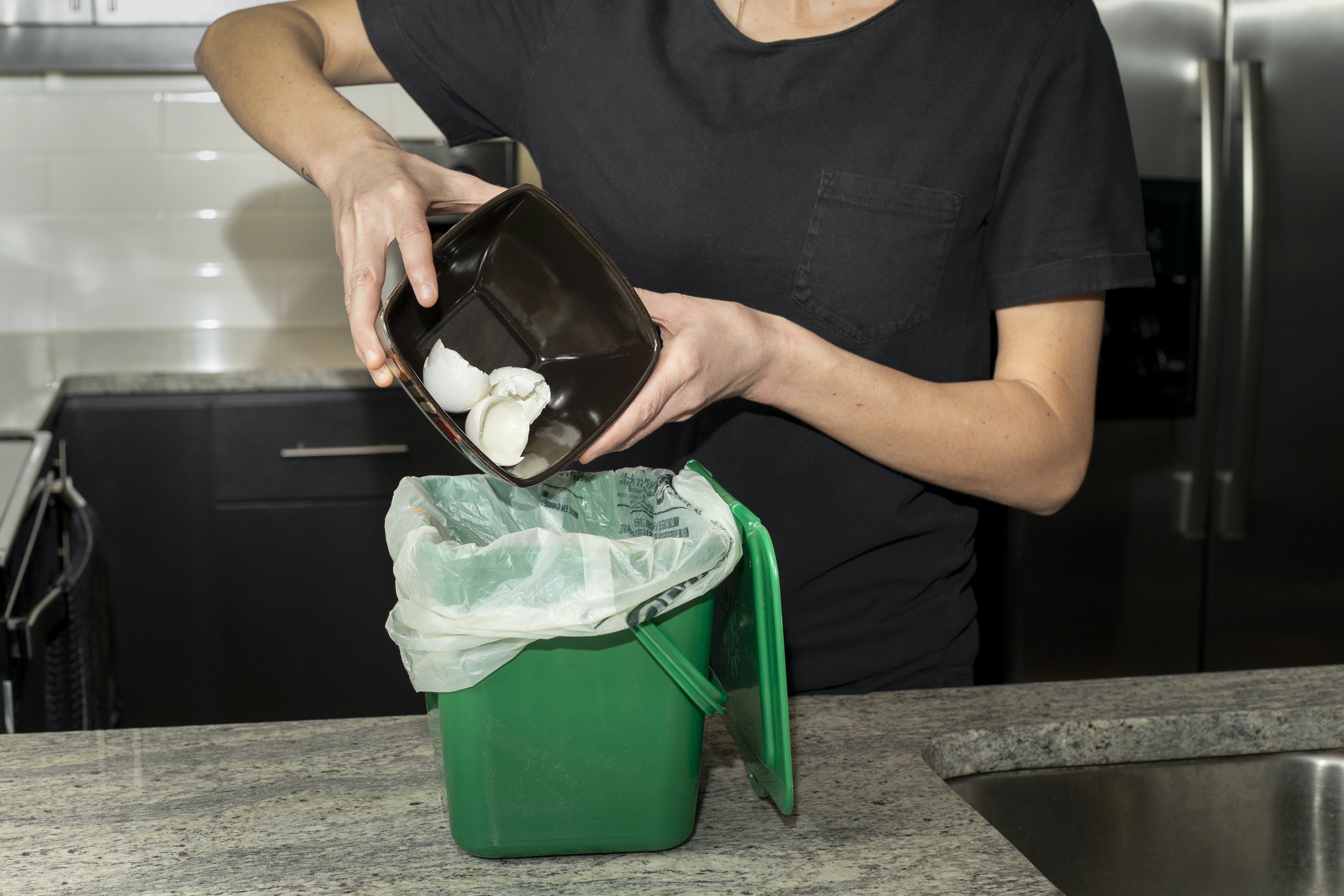 Organic materials like egg shells being placed in the kitchen container
