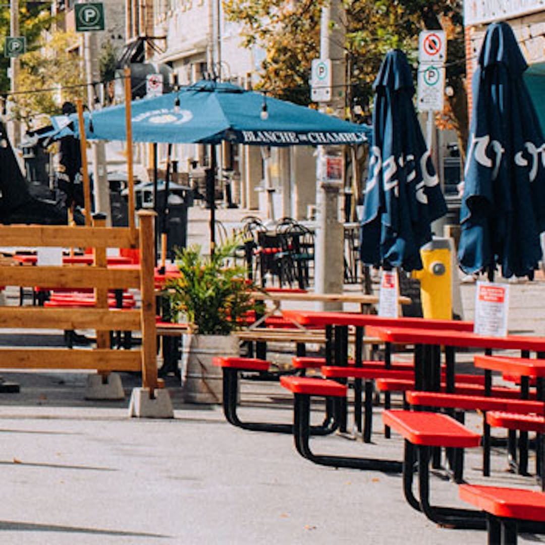 An image of patio seating and patio umbrellas along a Guelph street with the Basilica in the background.