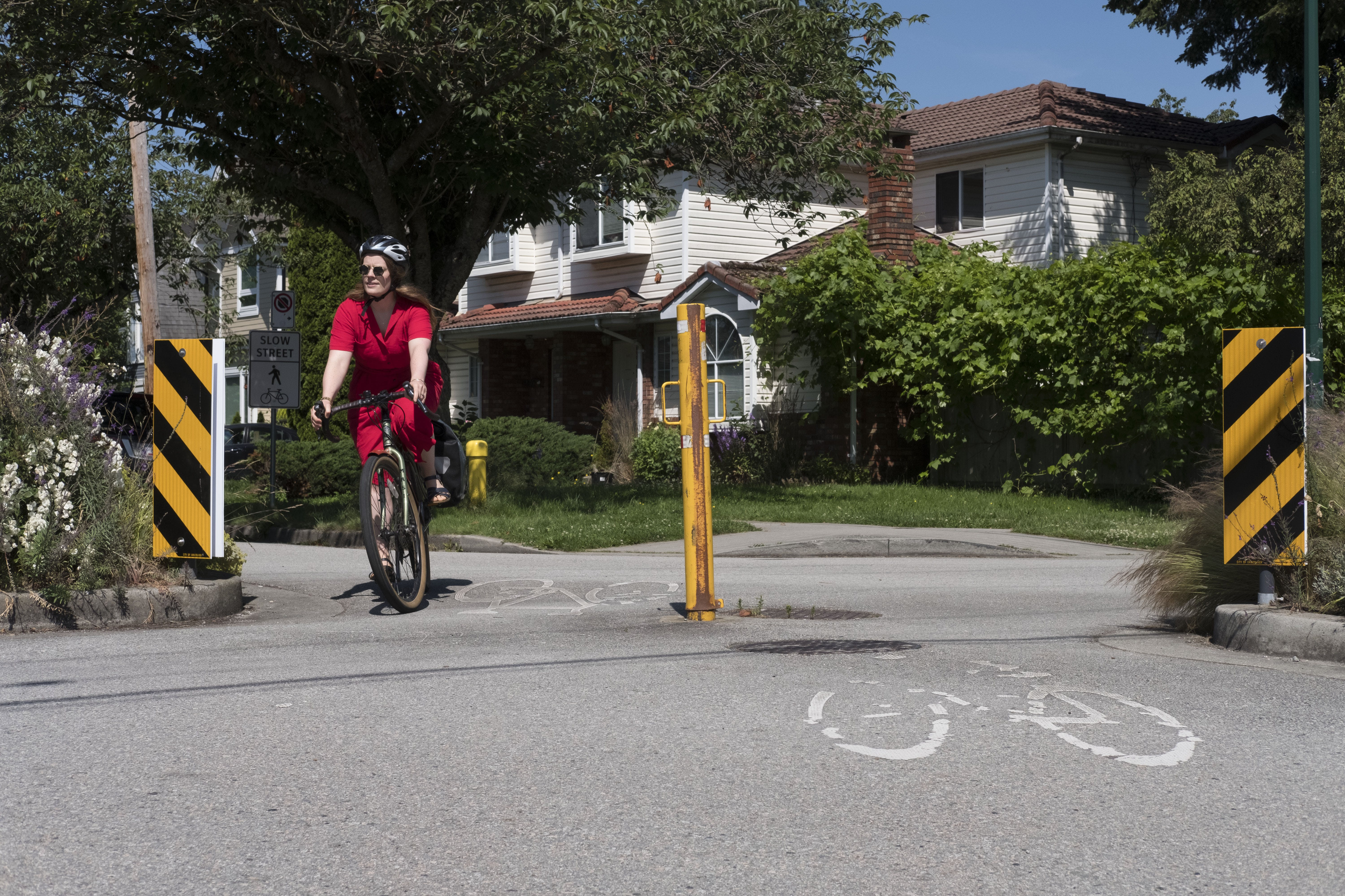 A cyclist in a red dress cycling along Slow Streets - Charles St at Lakewood Dr. Slow Streets connect neighbouring parks and open spaces.