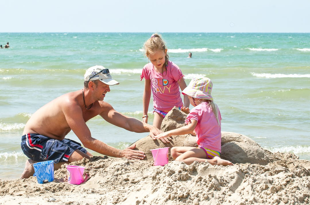 A white male adult builds a sandcastle with two white female children on a summer day at Sandbanks Beach