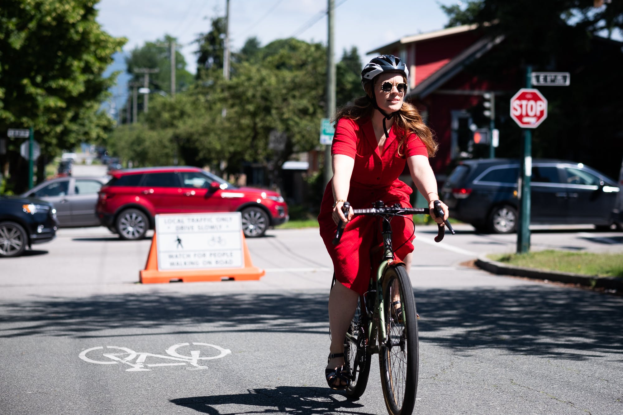 A cyclist in a red dress comfortably cycling along Slow Streets - Lakewood Drive.