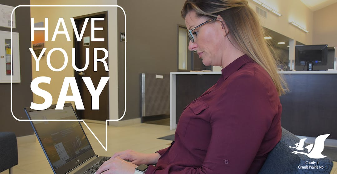 A woman using a laptop to participate online in the County of Grande Prairie's new website project.