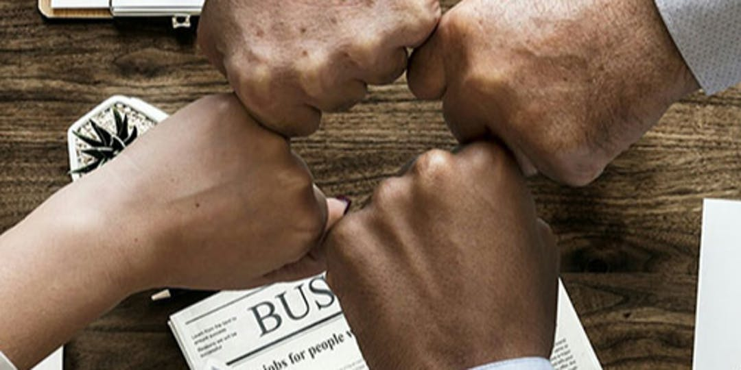 four fists together over a business table
