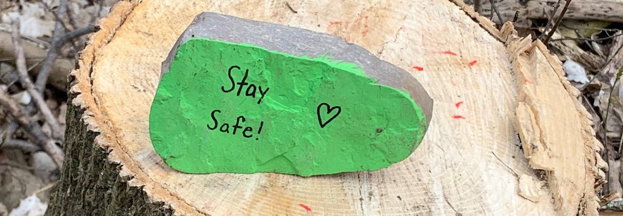 """Rock painted green with writing on it reading """"Stay Safe"""""""