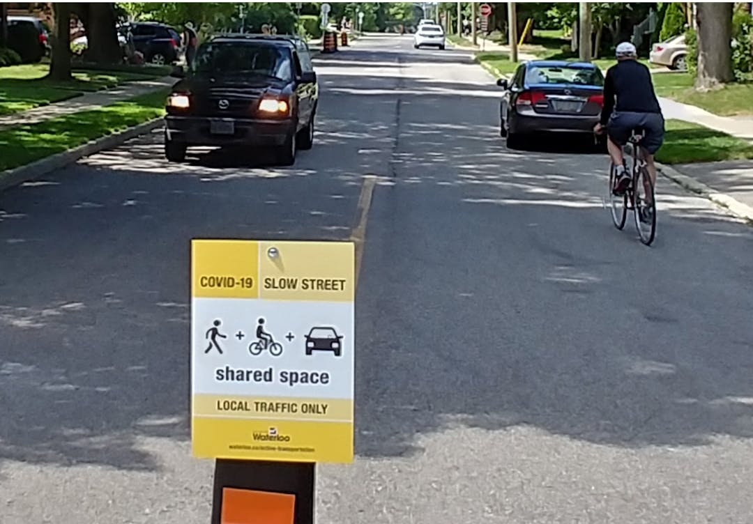 Slow street being used by car and bike, with sign indicating local traffic and shared space for pedestrians, cyclists and drivers.