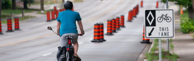 Cyclist driving on road in expanded bike lane with large construction pylons used as barrier.