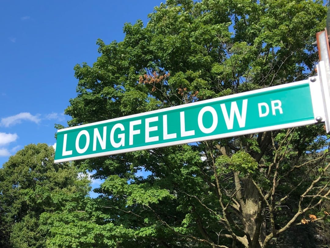 Longfellow Drive street sign with blue sky and mature trees in the background.