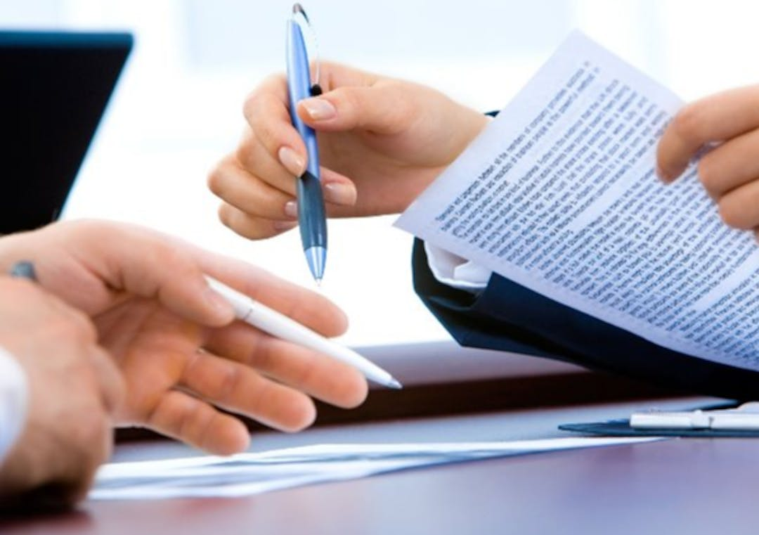 Photo of hands of two people reviewing a document
