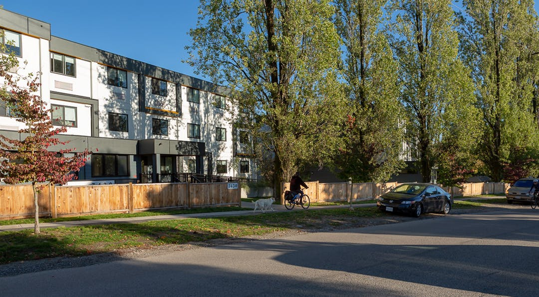 Example of modular-style supportive housing building in a community setting, with trees. Street view.
