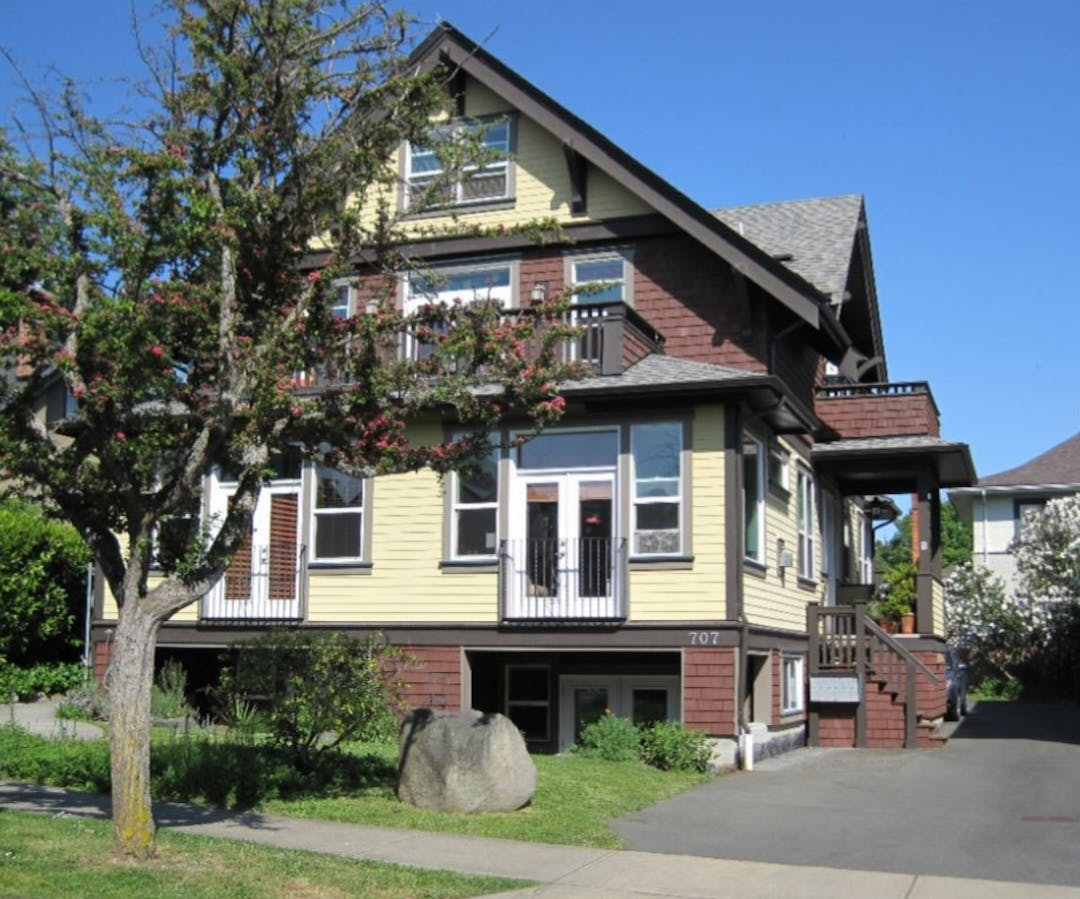 A large heritage home that has been converted into multiple housing units.