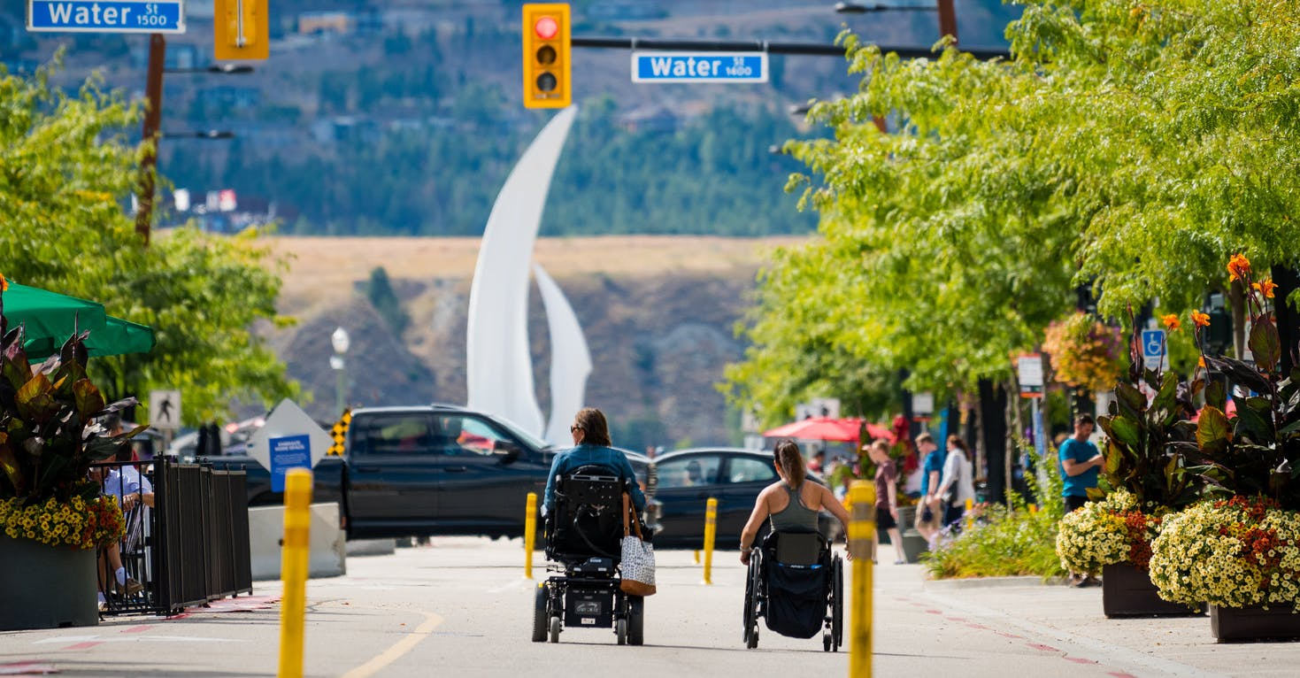 Two people with disabilities travel down Bernard Avenue in Kelowna