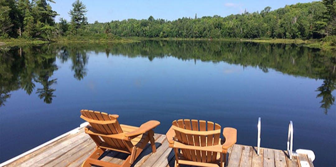 two muskoka chairs on dock overlooking glassy water