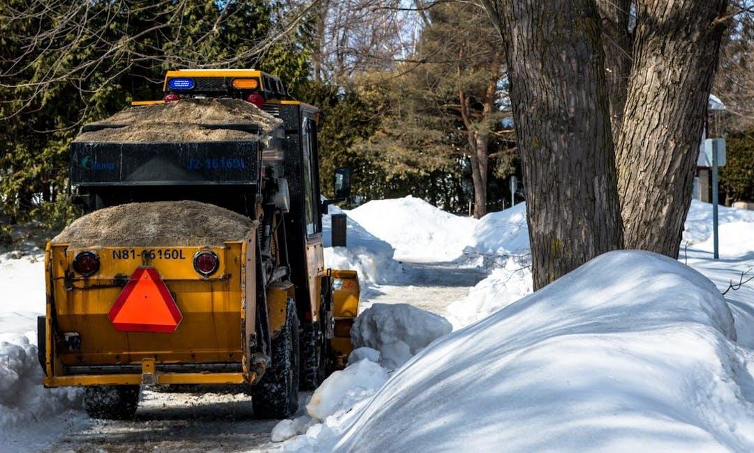 Plow clearing a snowy sidewalk