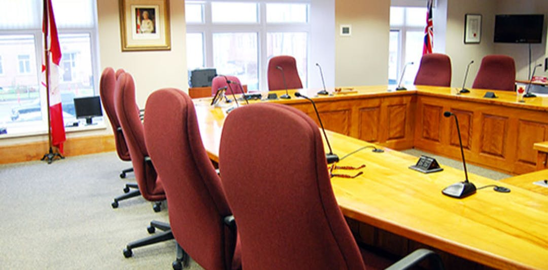 view of Council Chambers room - table, chairs, Canada Flag and Queen photo