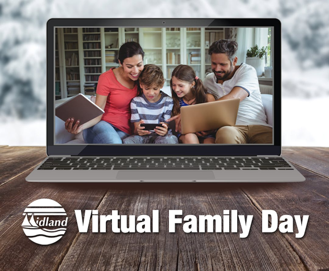 A laptop is open on a wood table, and the laptop screen has a photo of a family of four using a tablet, mobile phone and laptop while sitting on a couch. In the background you can see snow covered trees.