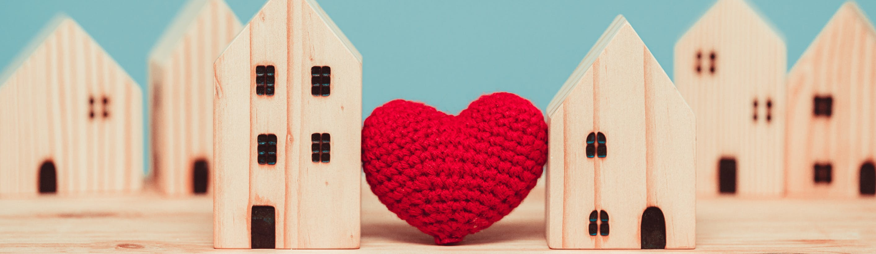 Red heart between two houses in wood model