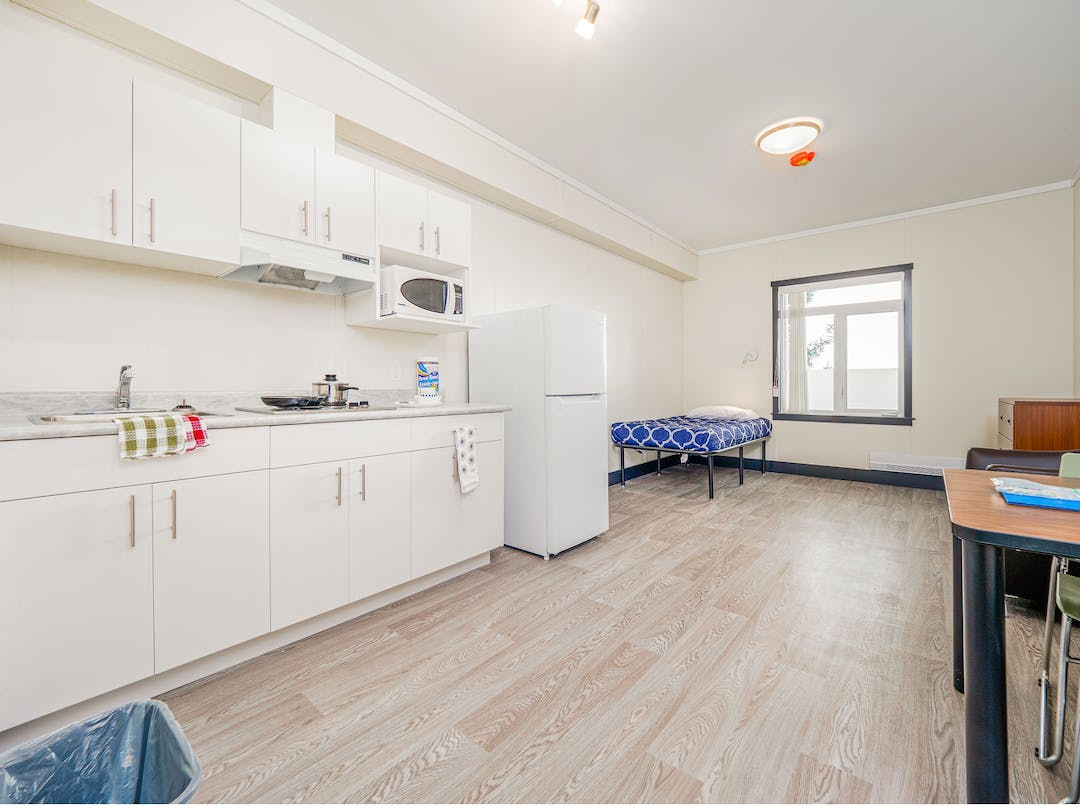 A unit in a supportive housing building, with a white kitchen and furniture.
