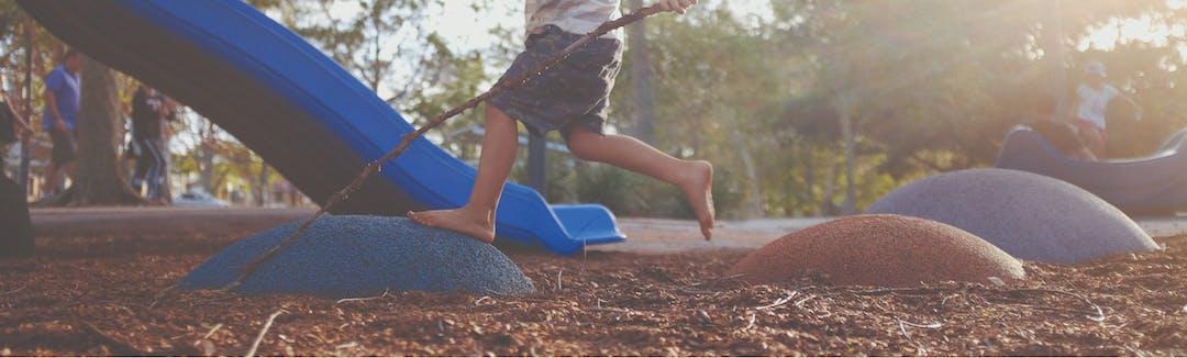 A child balances on play equipment.