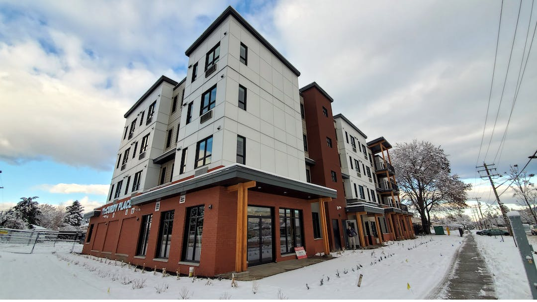 Exterior photo of new three-storey supportive housing building. Street view with snow.