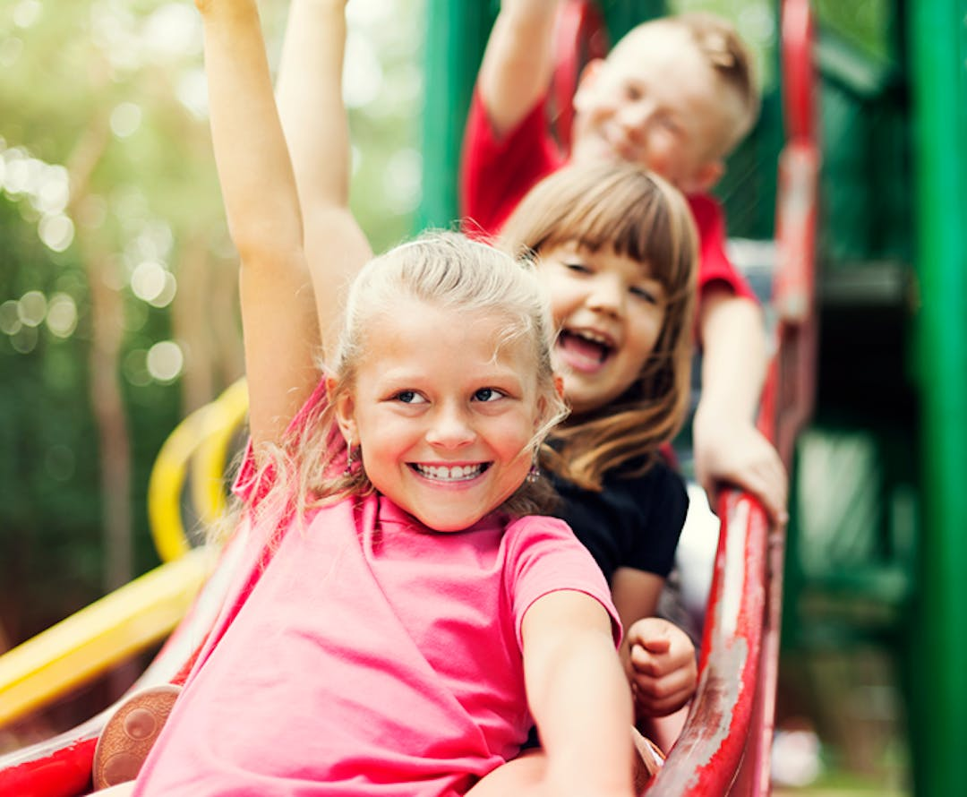 A picture of three children enjoying a slide,
