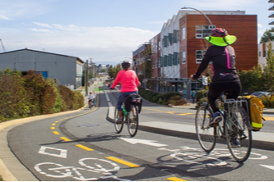 Two people bicycle on the Harbour Road bicycle lanes.