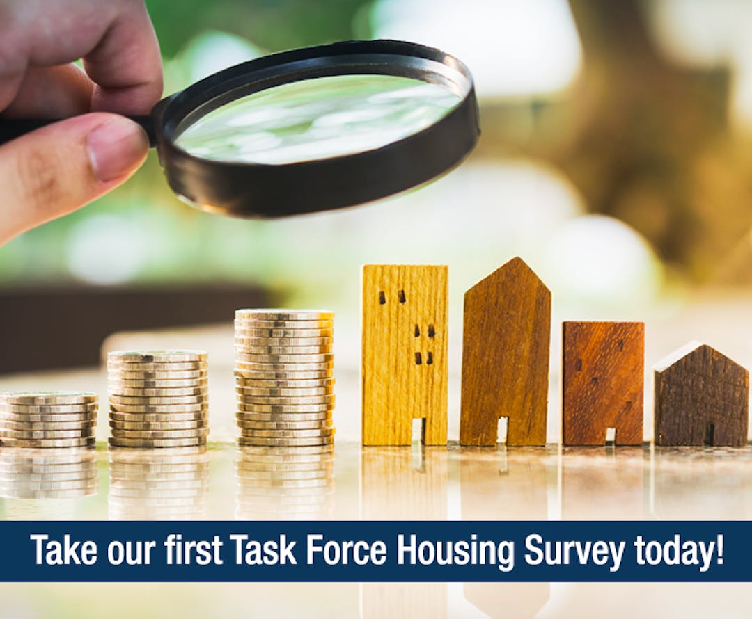 """A photo of a magnifying glass looking at some small model houses next to stacks of coins. A banner across the bottom of the images says """"Take our first Task Force Housing Survey today!"""""""
