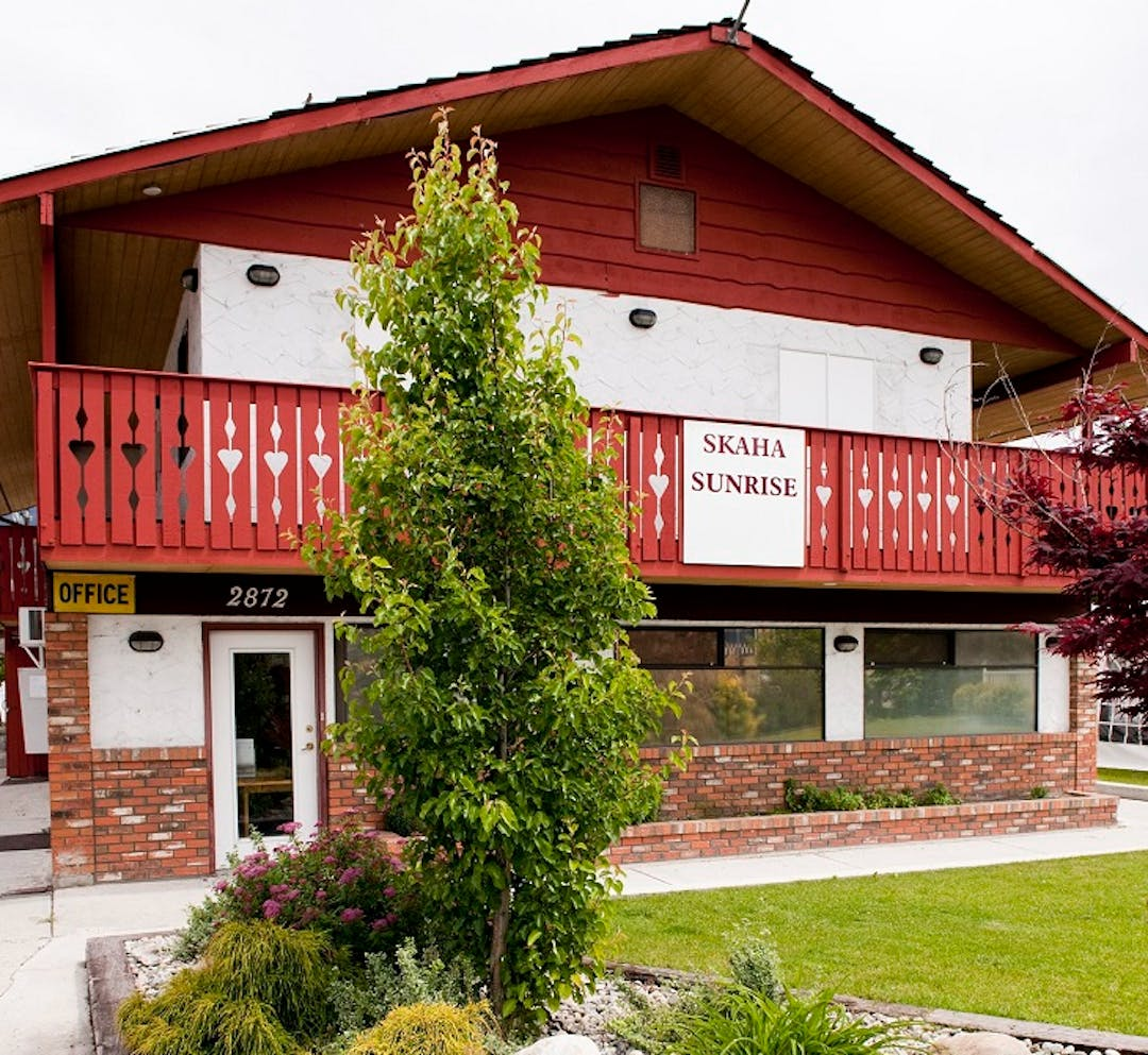 Street view of entrance of a former motel. Red and white exterior with brick façade. Glass door with landscaping along sidewalk.