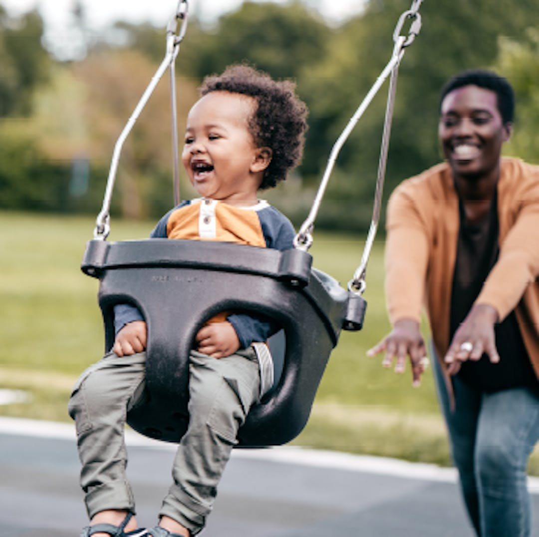 Child on a swing is playfully pushed by woman in the background