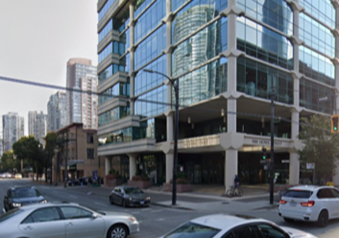 Image is an exterior photo of the proposed Renter Centre at 900 Howe St with cars at Smithe and Howe intersection