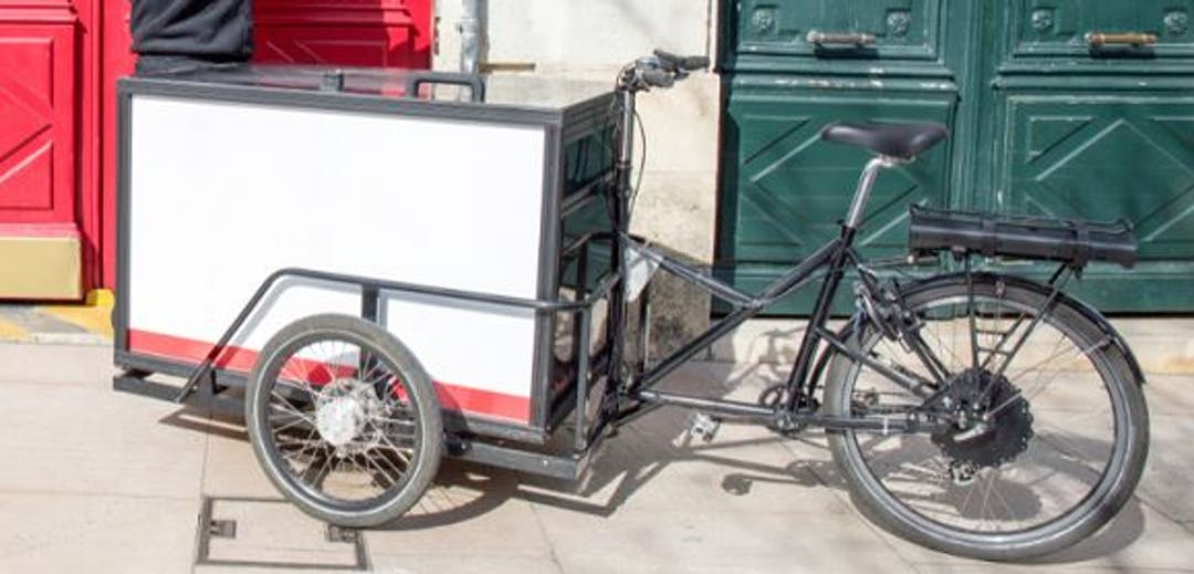 An image of a cyclist riding a large cargo e-bik