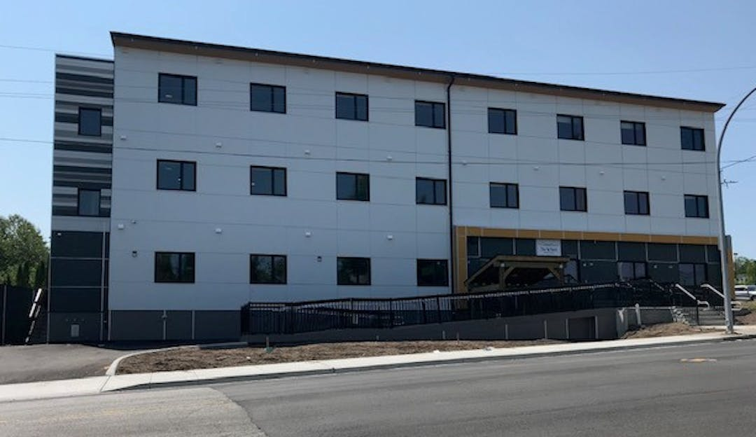 A white, three-storey supportive housing building on a clear day.