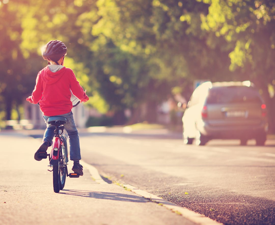 A small boy rides his bicycle along a calm, town road, as a minivan drives by.