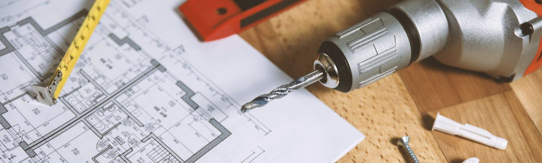 A wooden table with building plans, a screwdriver, measuring tape, and screws