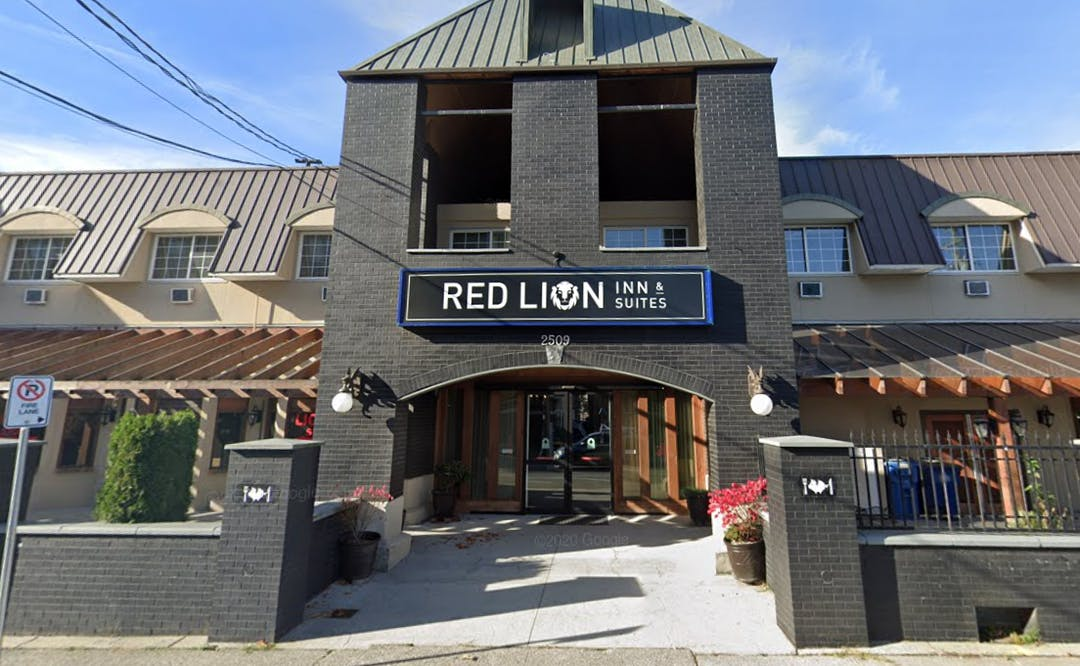 """A dark brick hotel with a sign that reads """"Red Lion Hotel."""""""
