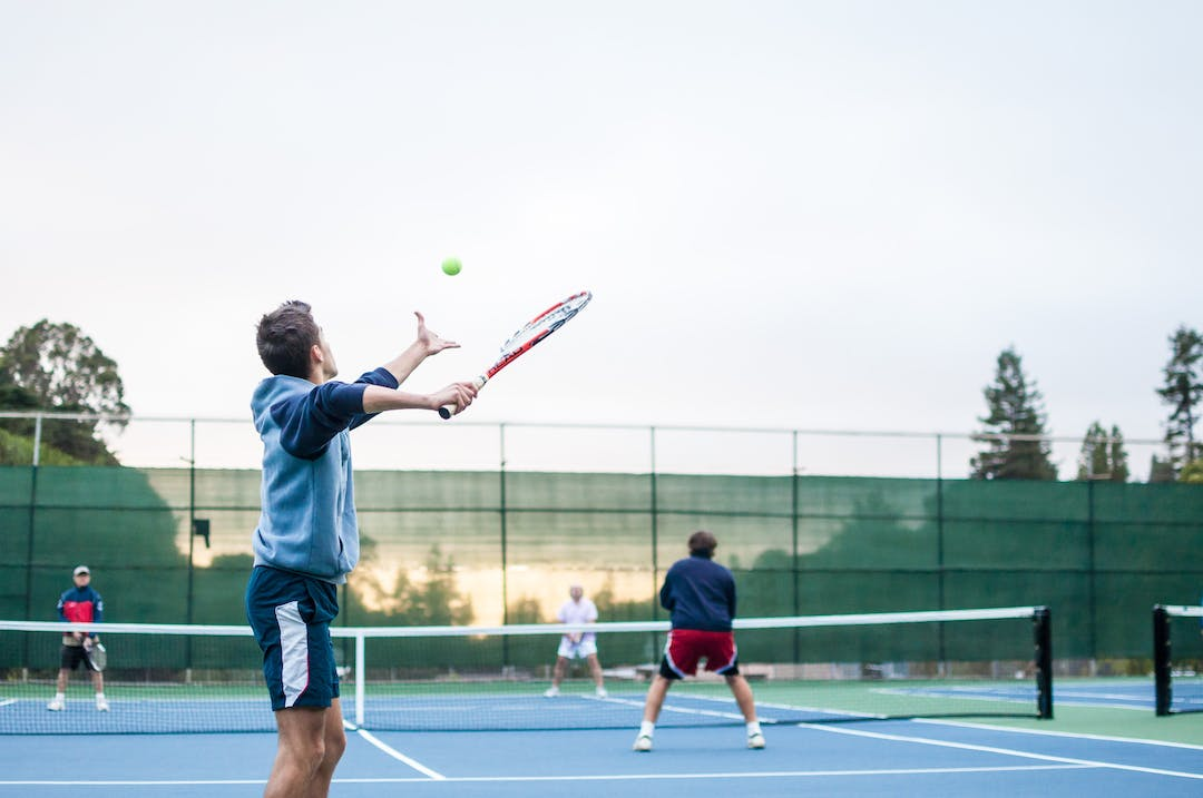 Four people playing tennis on a court.