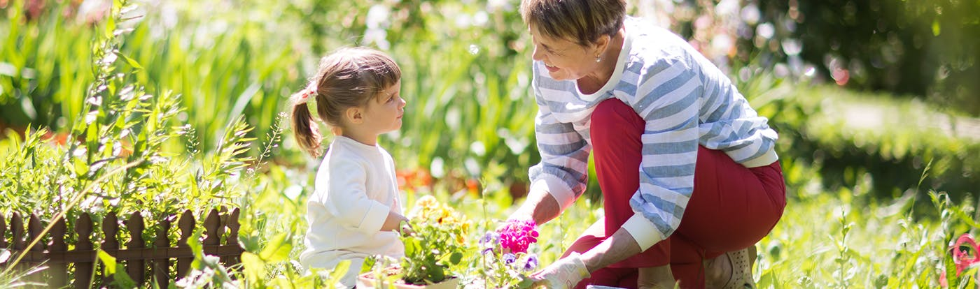Small, female child gardening with senior in sunny garden, both looking at one another smiling.