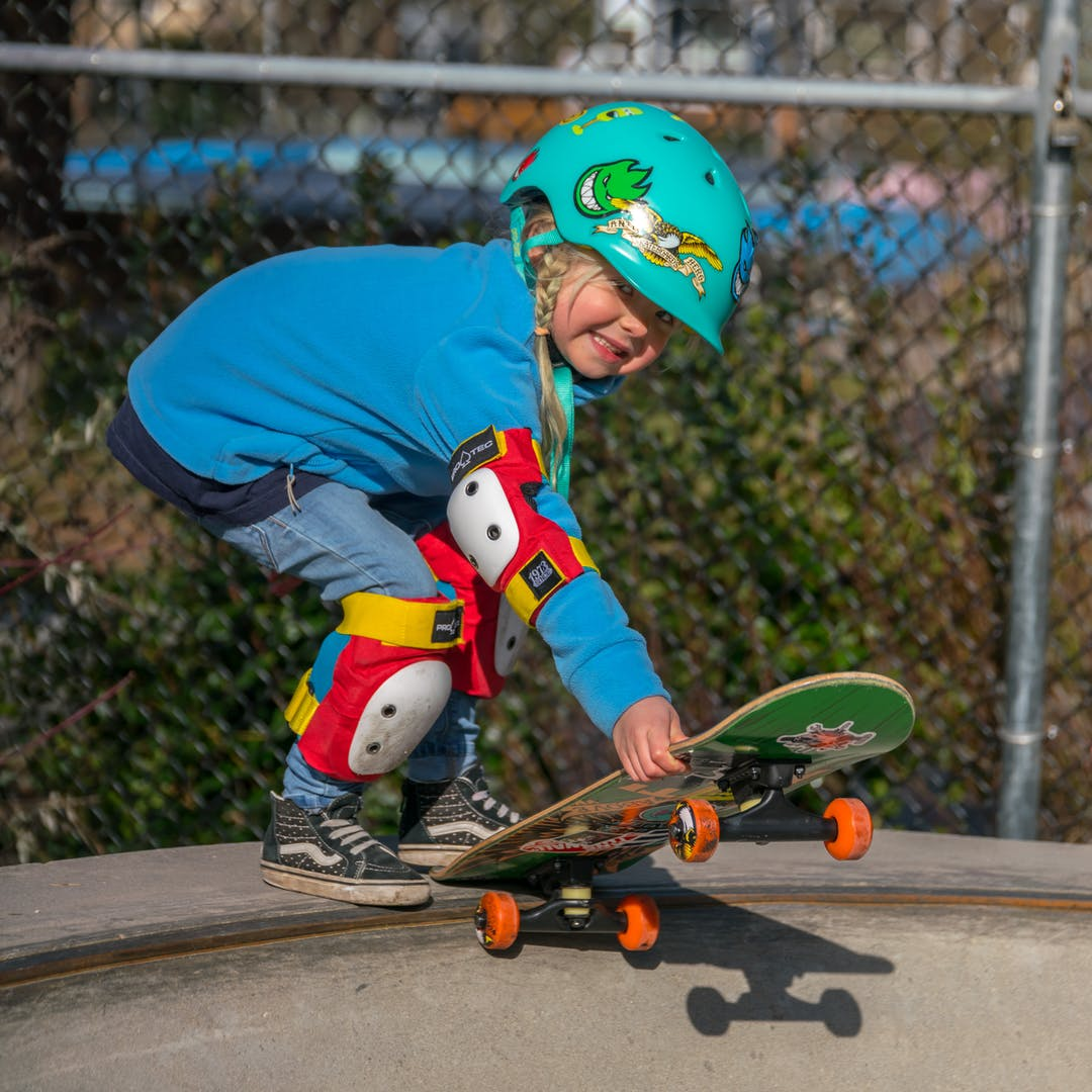 Young girl Ivy skateboarding at Mount Pleasant Skate Park on a sunny day with a big smile