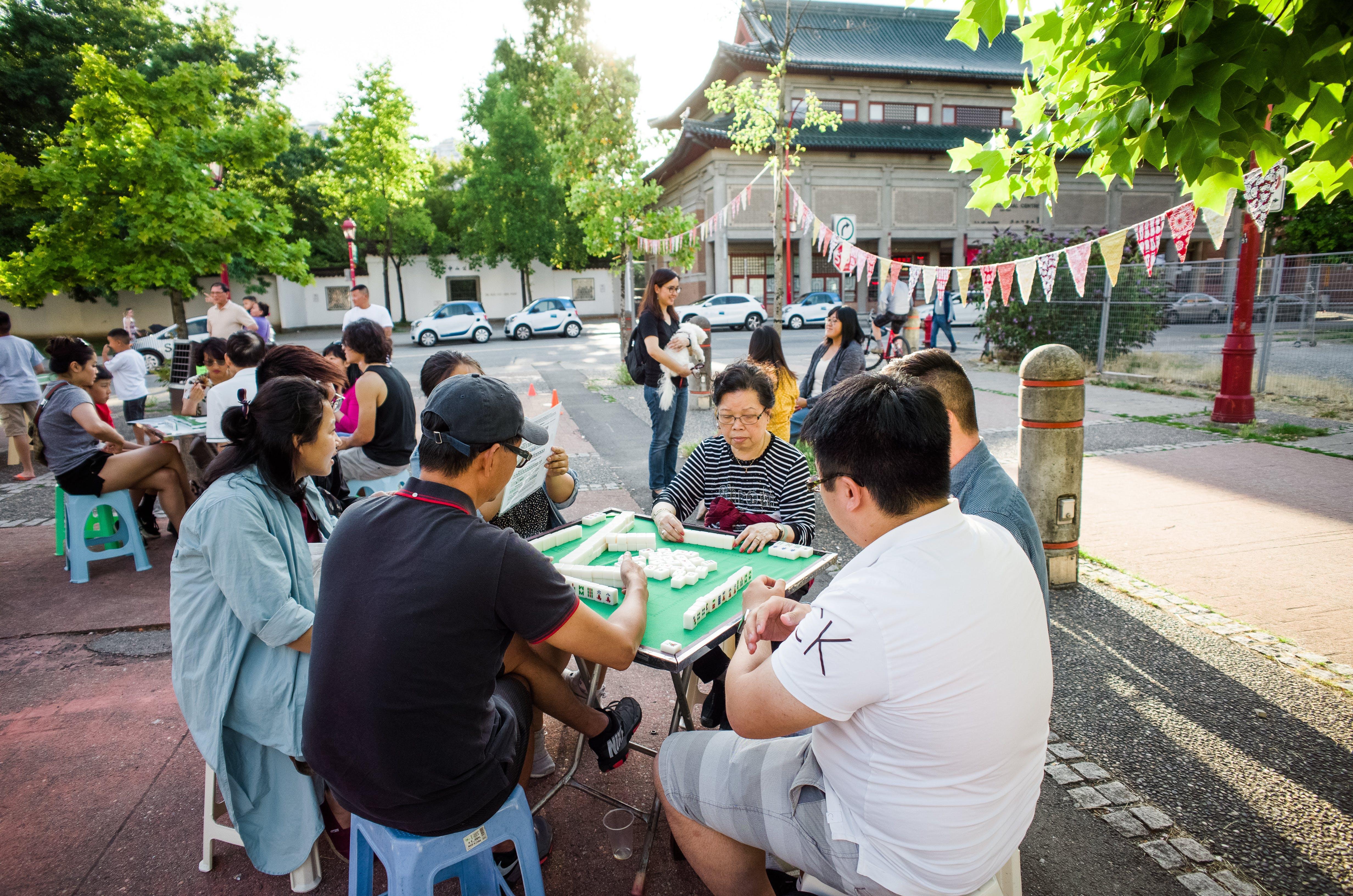 Several groups of youth and seniors playing mah jong at Memorial Square