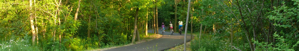 A family rides bicycles on a newly constructed portion of the East Don Trail