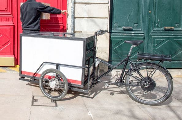 A reverse tricycle design with enclosed cargo box in the front