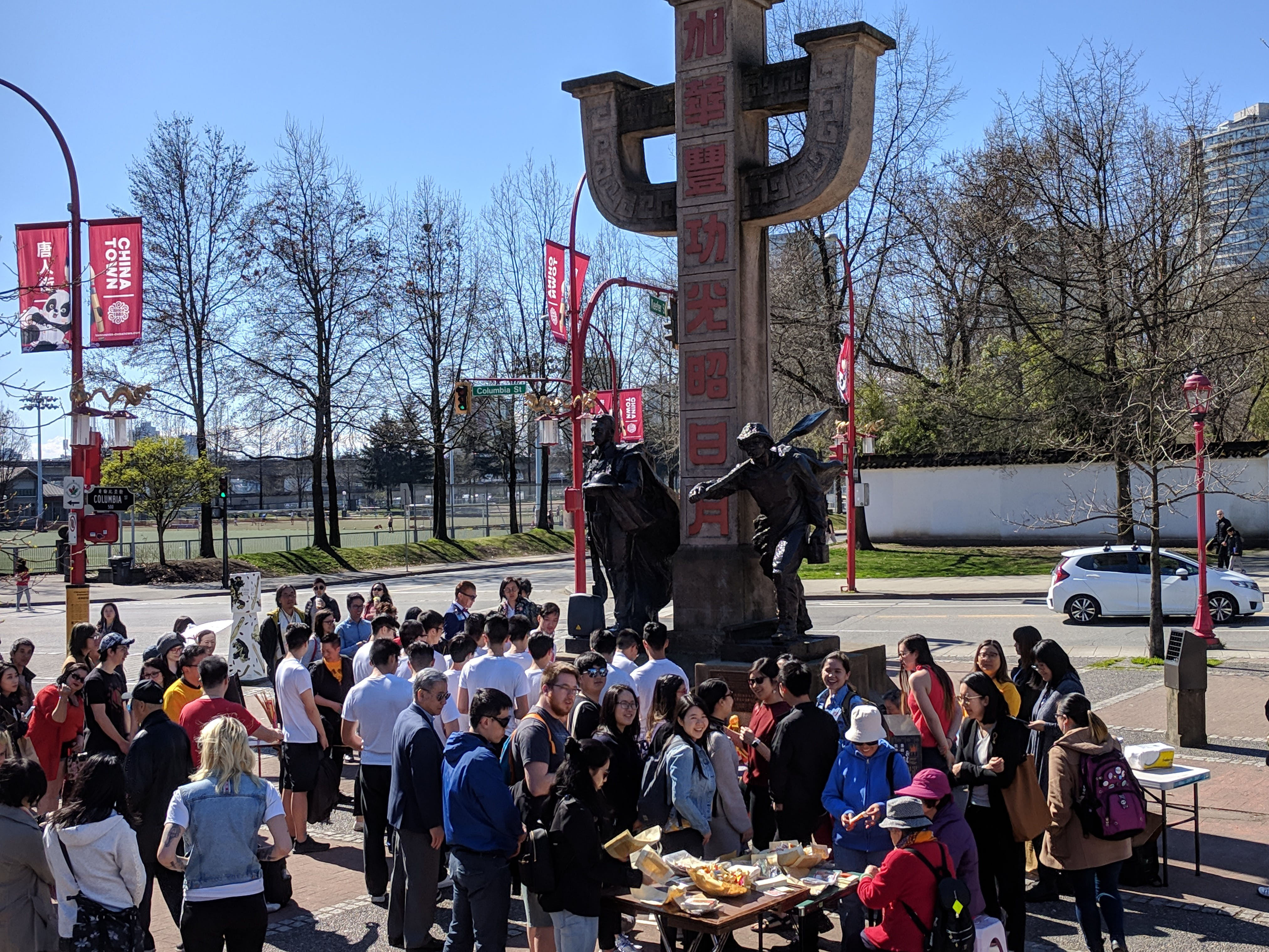 A youth group gathers on Memorial Square sharing food and socializing.