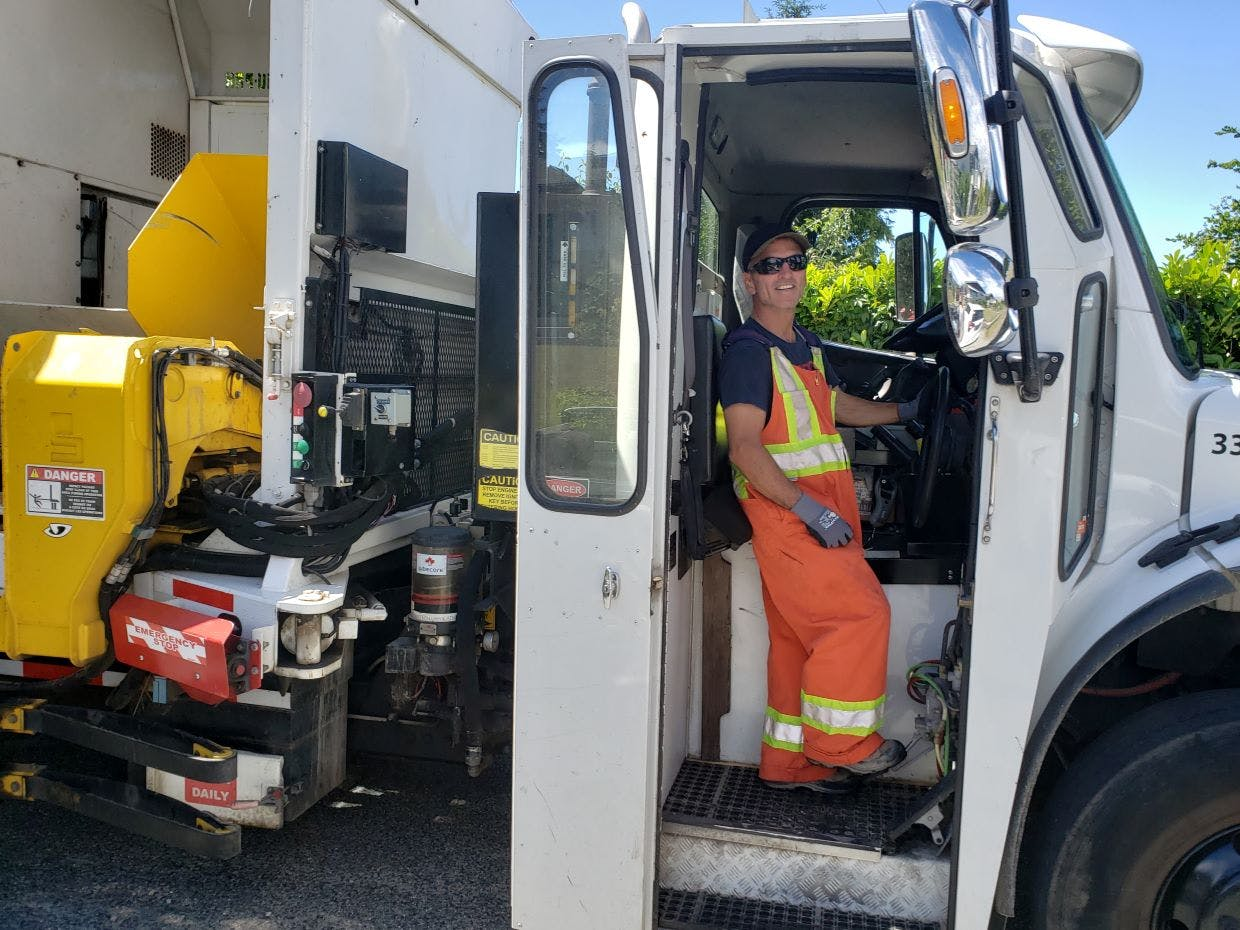 Public Works labourer, Yvon Sevigny, at the wheel of one of the City's automated garbage trucks.