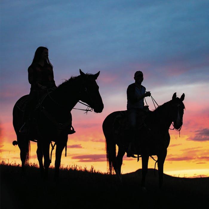 Silhouettes de deux personnes à cheval au coucher du soleil