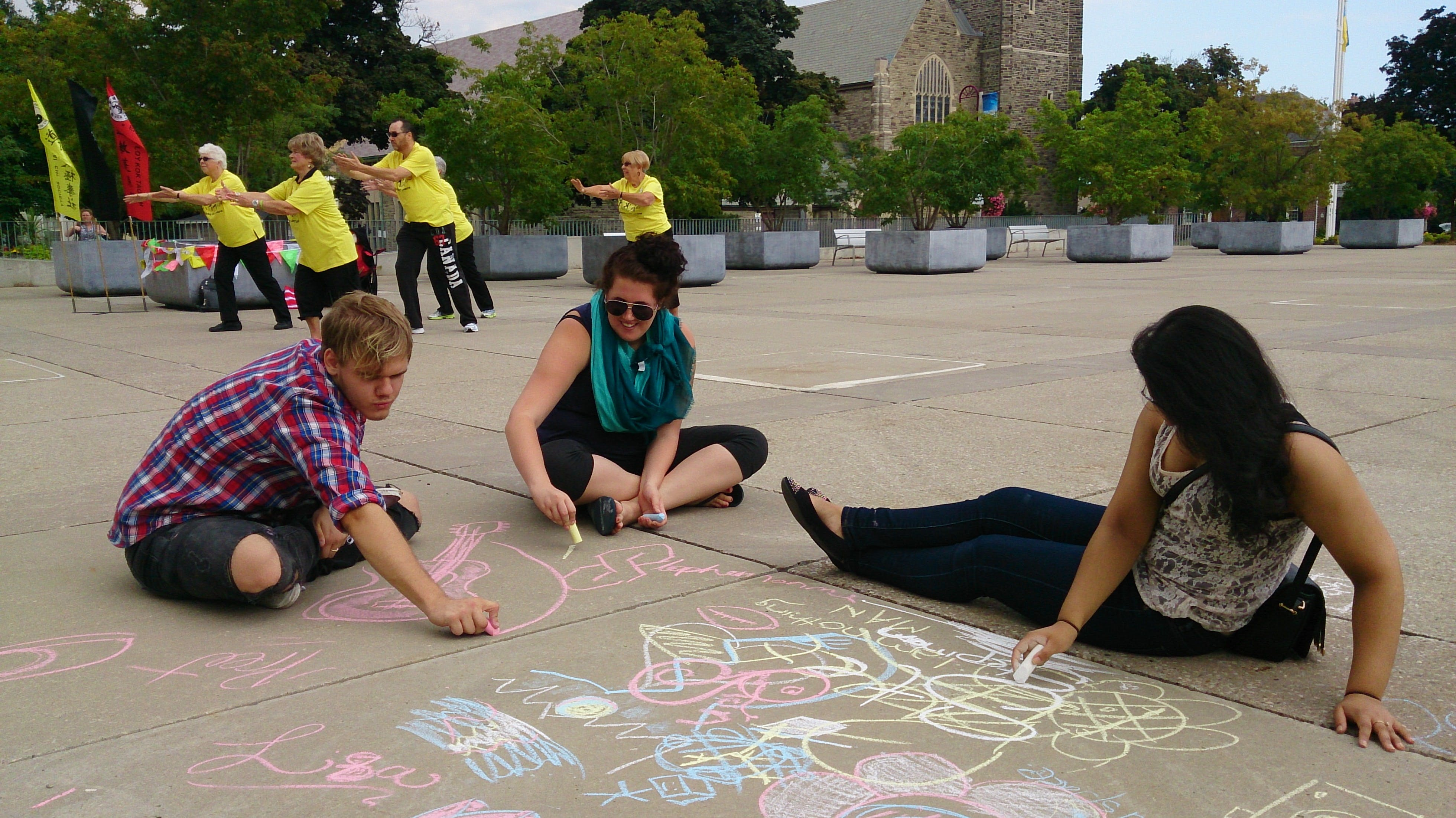 Residents participating in Tai Chi and playing with chalk in Civic Square at a Culture Night.