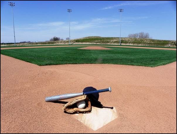 Image of a baseball bat, glove with ball and a hat on homeplate looking out on the Premier Baseball Diamond.