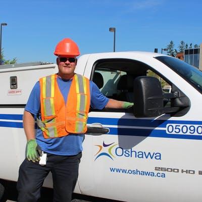 Dan standing in front of City of Oshawa traffic work truck.